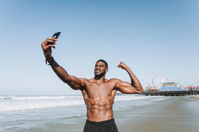 svalnatý muž robí selfie, pláž.jpg