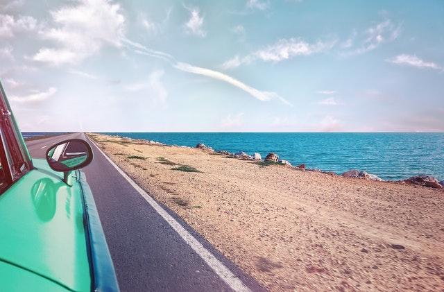 Auto idúce po ceste popri pláže amori za slnečného počasia.jpg