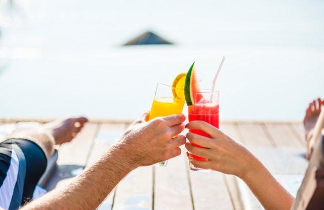 Muž a žena si štrngajú s kokteilmi na terase s výhľadom na more.jpg