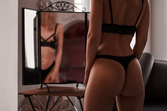 Žena v čiernej spodne bielizni, stojaca pred zrkadlom