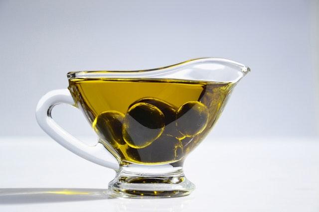Sklenená miska s olivovým olejom a zelenými olivami