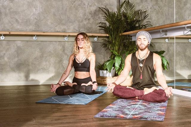 Žena a muž sedia na karimatkách a cvičia jogu.jpg