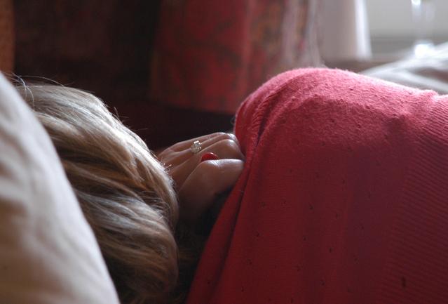 Žena leží v posteli zabalená do paplónov.jpg
