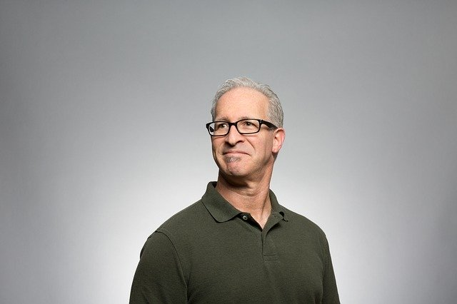 Muž v okuliaroch, so sivými vlasmi, v zelenom tričku sa usmieva.jpg