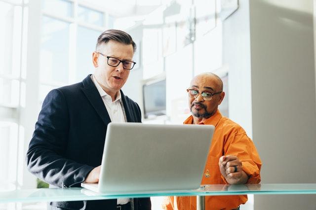 Dvaja podnikatelia, biely laptop